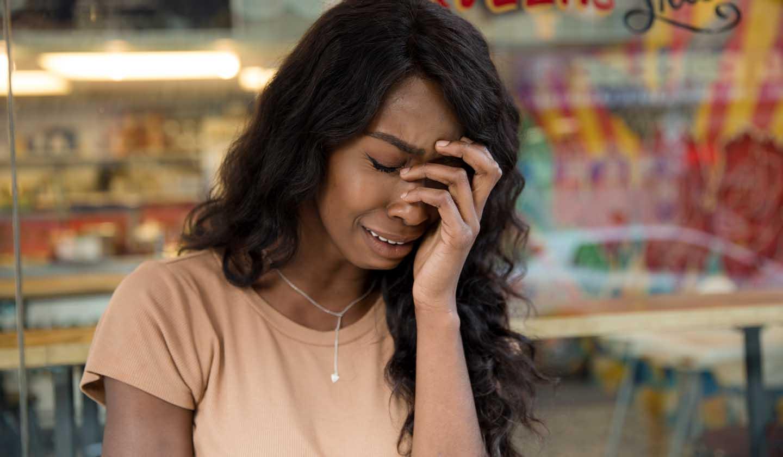 Uma mulher com burnout chorando.